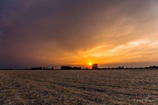 Die hereinziehende Wolkenfront lässt den Sonnenuntergang zunehmend düsterer erscheinen